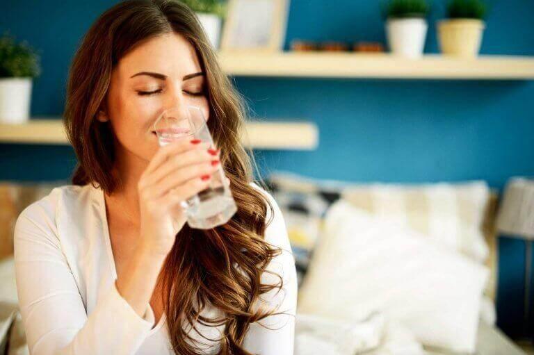 γυναίκα που πίνει νερό, πώς θα ελέγξετε τη γαστρίτιδα με σπιτικά κόλπα