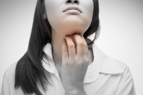 Τι είναι τα τσάκρα - Γυναίκα πιάνει τον λαιμό της