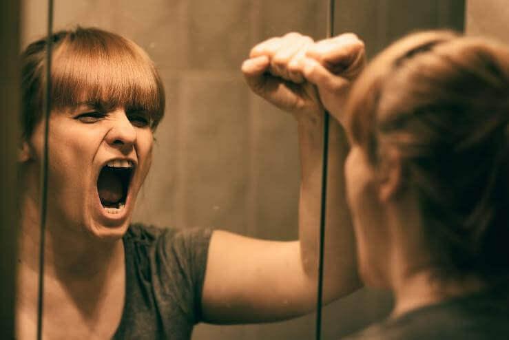 γυναίκα που φωνάζει μπροστά σε καθρέφτη