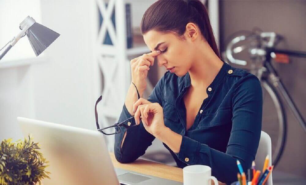 γυναίκα στο γραφείο κρατώντας γυαλιά, για το χαμηλό αριθμό αιμοπεταλίων