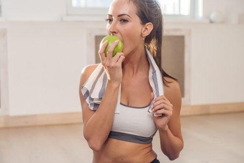γυναίκα με αθλητικό τοπ τρώει μήλο
