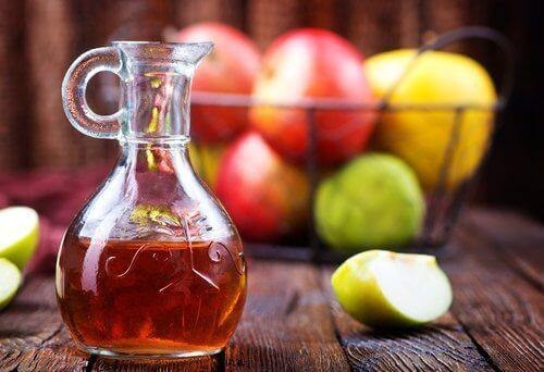 μηλόξυδο σε γυάλινο μπουκάλι και μήλα σε μπολ- μύκητες του δέρματος