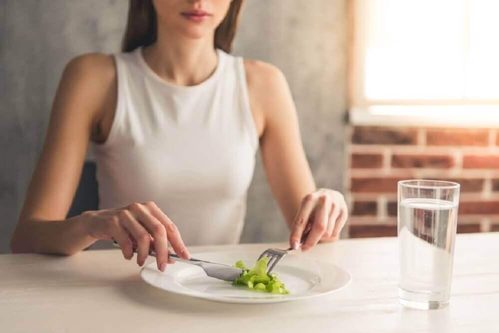 γυναίκα που τρώει ένα φύλλο μαρούλι, αδυνάτισμα χωρίς πείνα