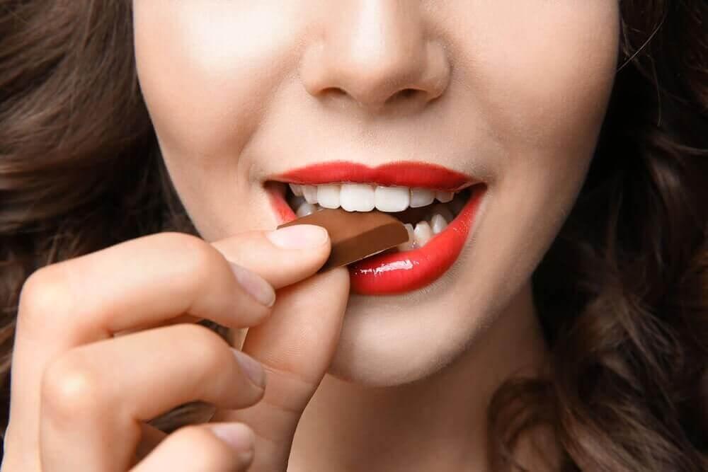 γυναίκα που τρώει ένα κομμάτι σοκολάτα, αδυνάτισμα χωρίς πείνα