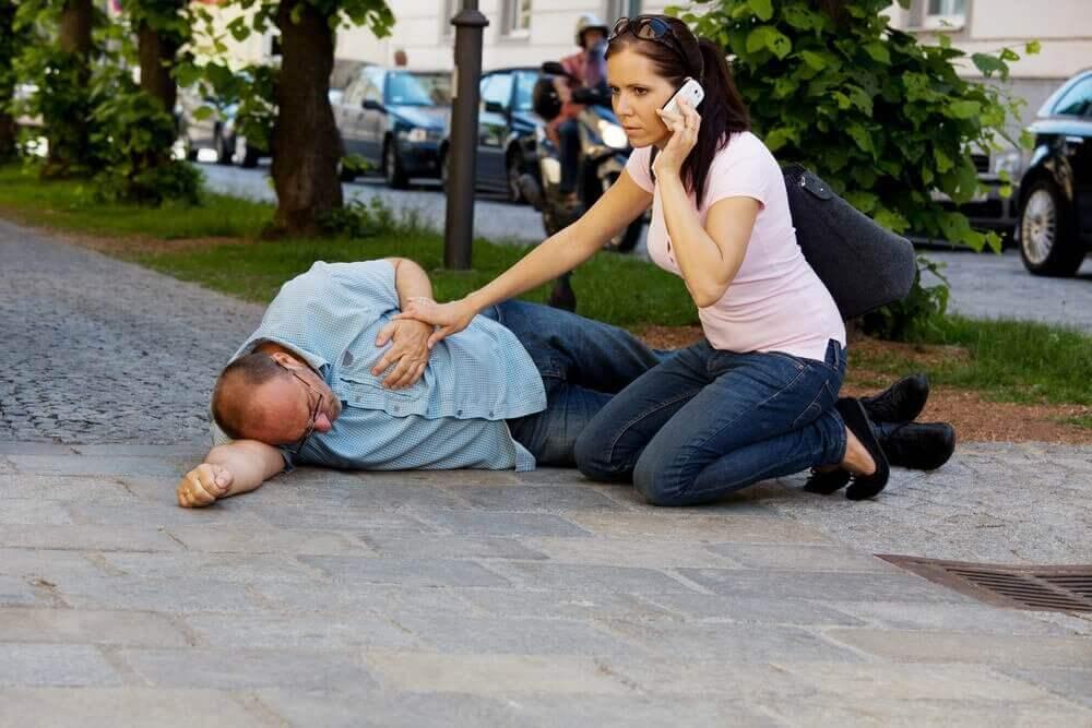 άνδρας πεσμένος κάτω και γυναίκα που τηλεφωνεί
