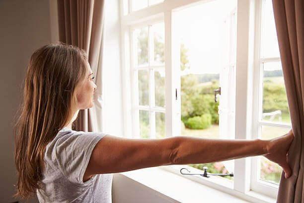 Γυναίκα που ανοίγει το παράθυρο, καταπολέμηση της θλίψης.