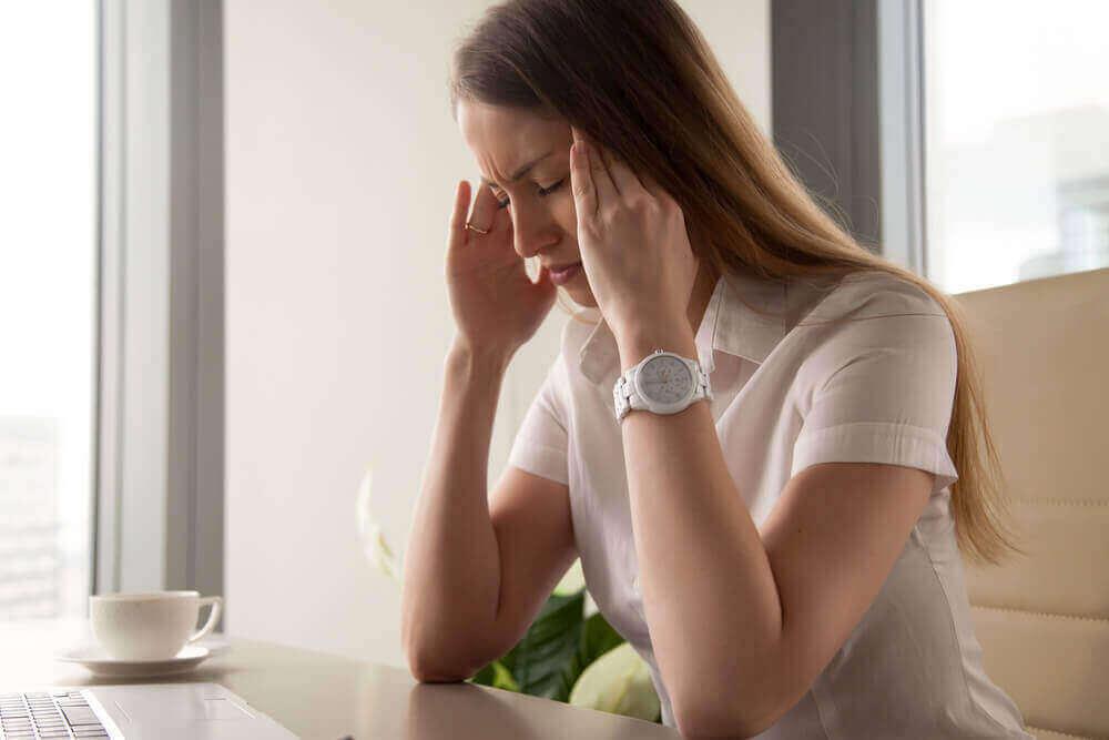 γυναίκα με πονοκέφαλο μπροστά σε λαπτοπ