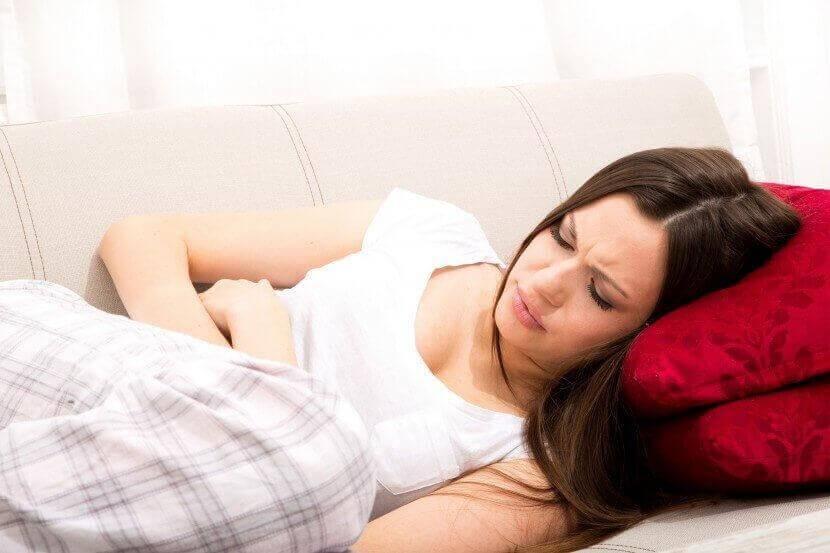 κράμπες περιόδου σε γυναίκα ξαπλωμένη σε καναπέ