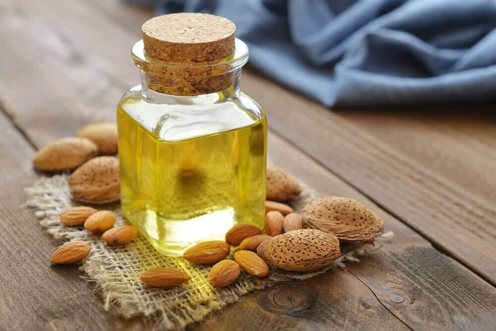 αμυγδαλέλαιο σε γυάλινο μπουκάλι και καρύδια