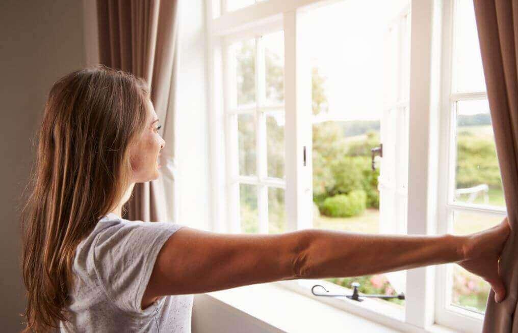 γυναίκα που ανοίγει το παράθυρο