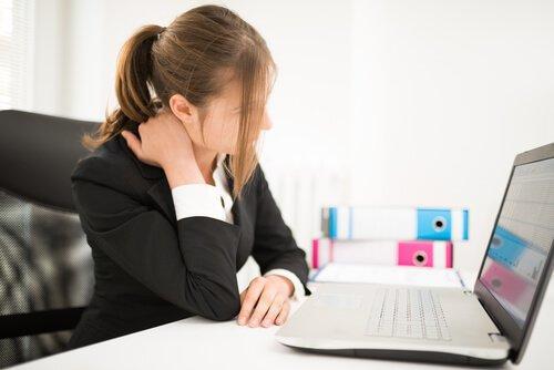 Αντιμετωπίστε τον μυοσπασμό στον αυχένα - Γυναίκα κάθεται μπροστά από υπολογιστή