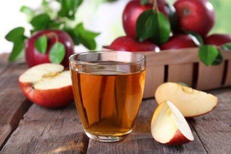 Μηλόξυδο σε γυάλινο ποτήρι και φέτες μήλου, πόδια που μυρίζουν
