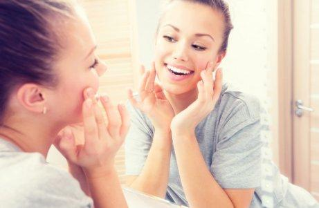 γυναικά που κοιτάζεται στο καθρέπτη και χαμογελά