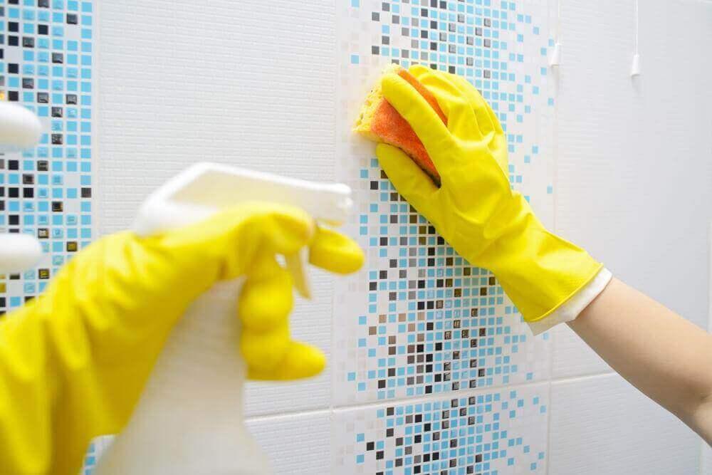 χέρια με γάντια που καθαρίζουν πλακάκια