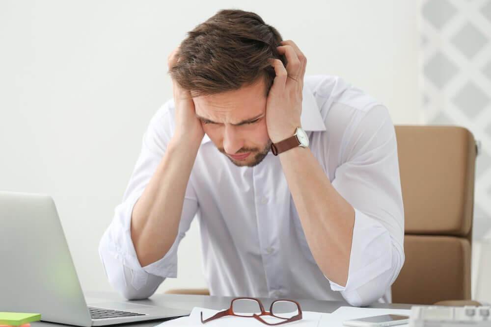 Αιτίες πονοκεφάλων - Άνδρας στο γραφείο με πονοκέφαλο