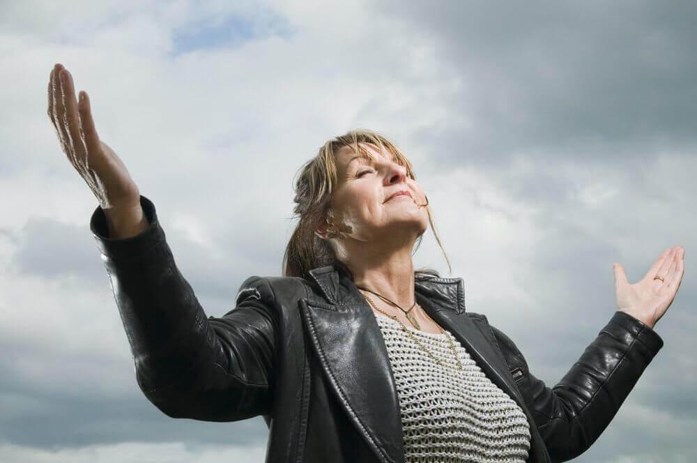 Κρίση της μέσης ηλικίας - Γυναίκα κοιτά ψηλά με ανοιχτά χέρια