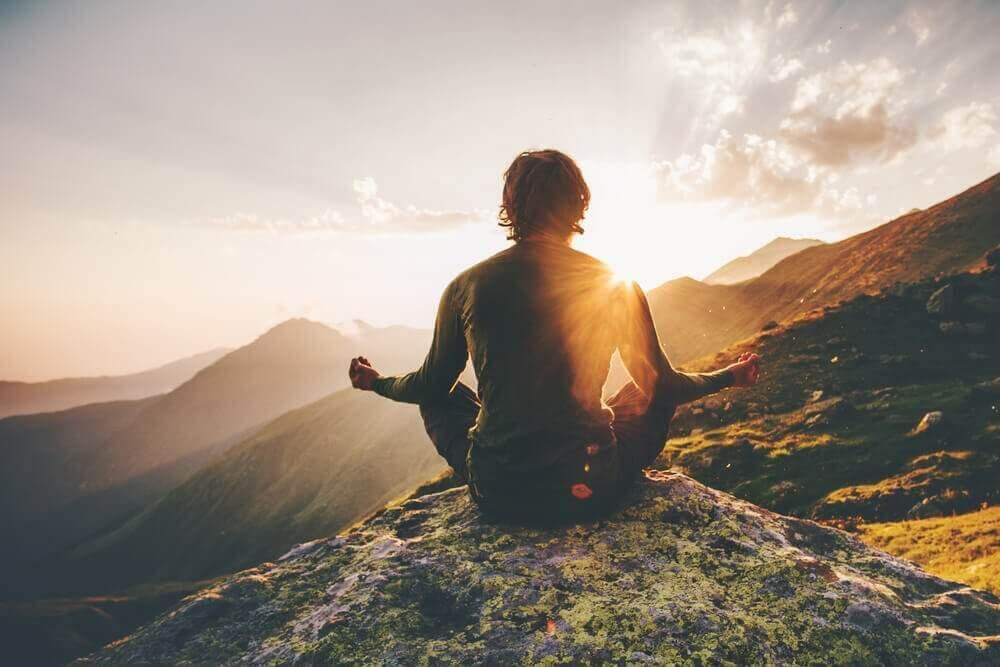 προσελκύσετε θετική ενέργεια άνδρας που διαλογίζεται στην κορυφή βουνού