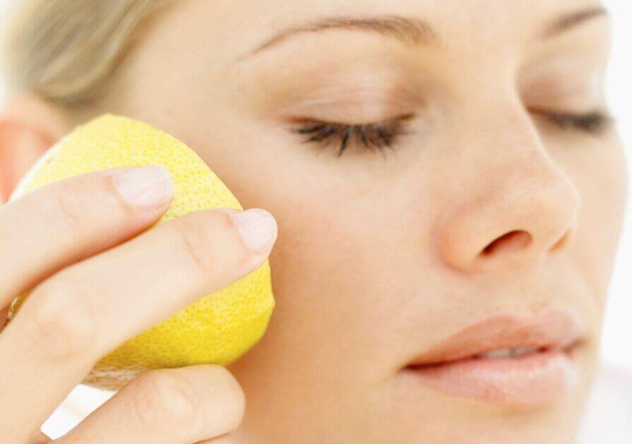 γυναίκα που βάζει λεμόνι στο πρόσωπο, λεμόνι ως φυσικό καλλυντικό