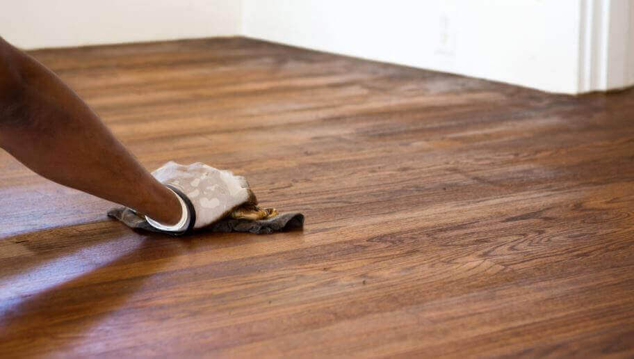 χέρι που καθαρίζει τα ξύλινα δάπεδα, λαμπερά δάπεδα