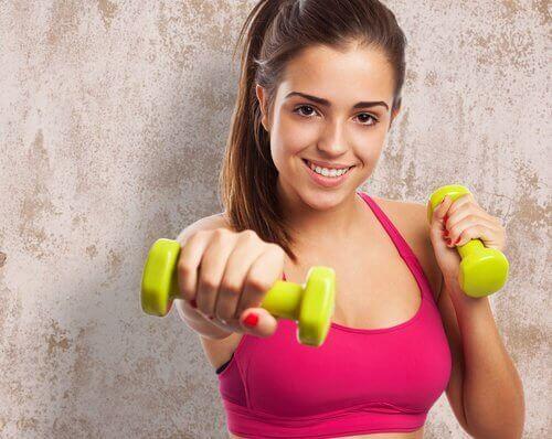 κοπέλα που κάνει άσκηση με βαράκια γυναικείες προβληματικές περιοχές