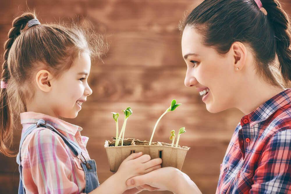 μητέρα με κόρη που της δίνει ένα φυτό- σούπερ μαμά