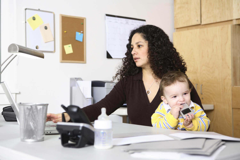 μαμά στο γραφείο που κρατάει αγκαλιά το παιδί -σούπερ μαμά