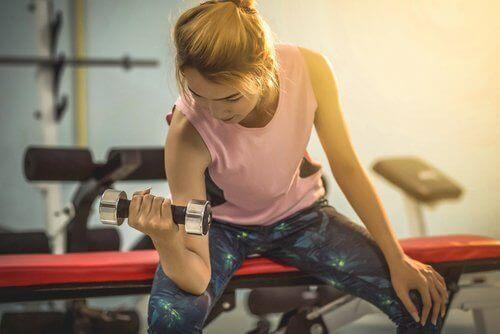 Γυναίκα κάνει ασκήσεις με αλτήρες, φαγητό και άσκηση