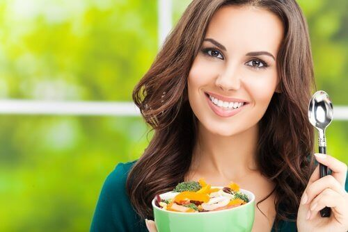 Γυναίκα κρατάει μπολ με λαχανικά, φαγητό και άσκηση