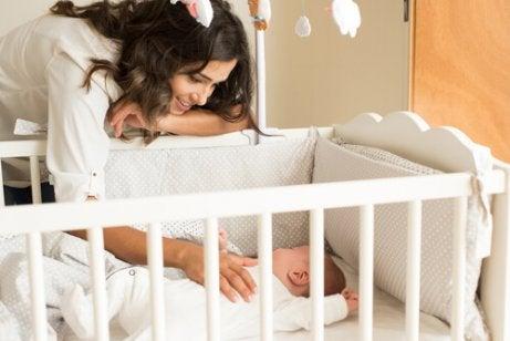 Γυναίκα πάνω από κούνια με μωρό- Μάθετε στο παιδί σας να κοιμάται όλη τη νύχτα.