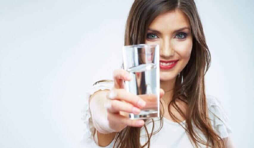Γυναίκα που κρατάει ποτήρι με νερό