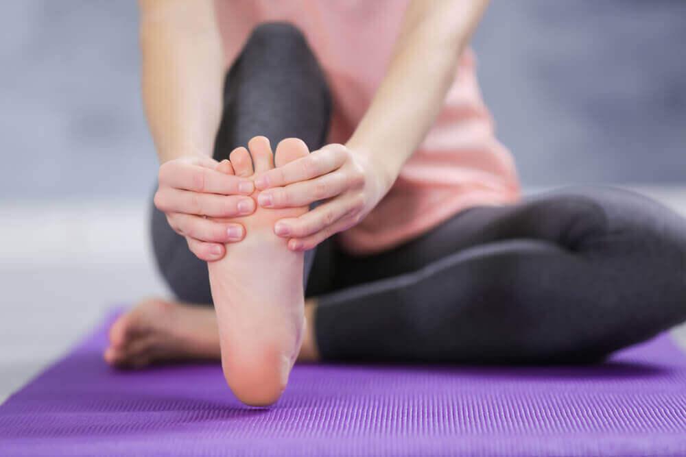 Γυναίκα τεντώνει τα δάκτυλα του ποδιού της προβλήματα που προκαλούνται στα πόδια από τις σαγιονάρες
