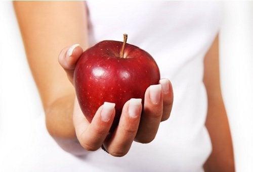 Συνταγές με ανανά - Γυναίκα που κρατάει κόκκινο μήλο