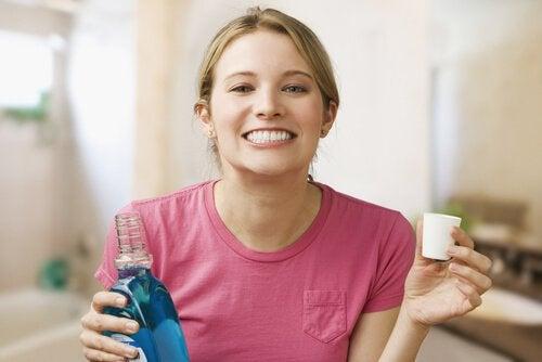 Γυναίκα χαμογελά κρατώντας στοματικό διάλυμα- λοιμώξεις στα ούλα