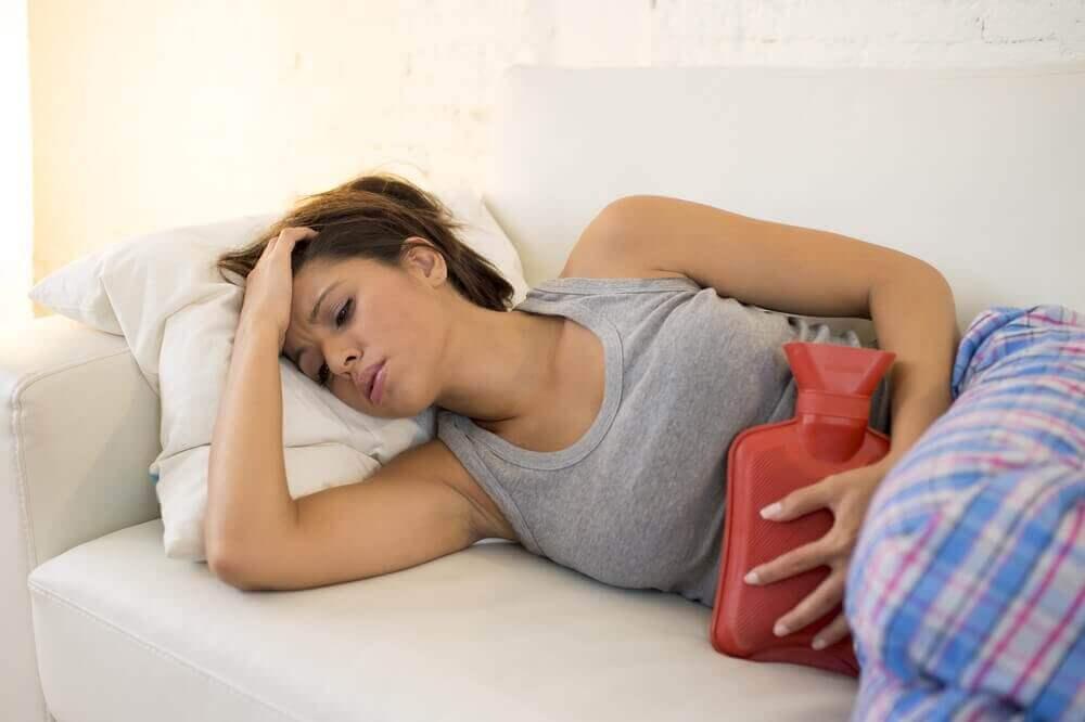 Συμπτώματα συνδρόμου πολυκυστικών ωοθηκών - Γυναίκα με θερμοφόρα στην κοιλιά