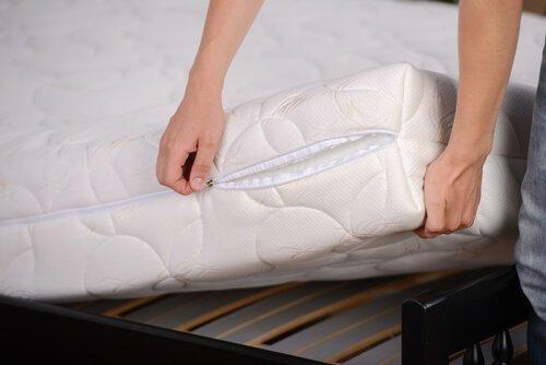 Απολυμάνετε το υπνοδωμάτιό σας - Άτομο αφαιρεί το κάλυμμα του στρώματος