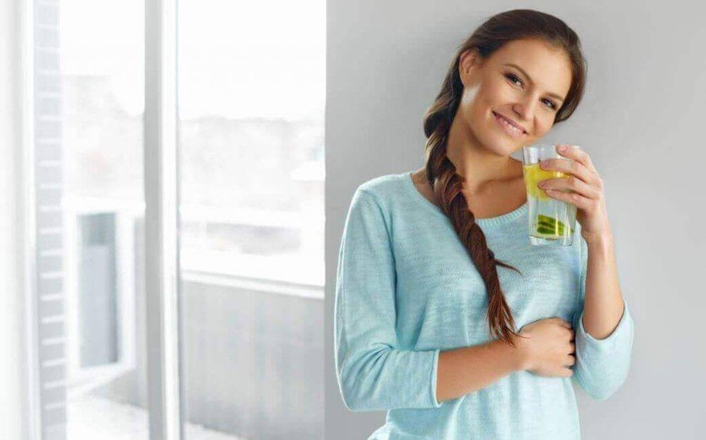 Νερό με λεμόνι και λιναρόσπορο - Γυναίκα πίνει νερό με λεμόνι και αγγούρι