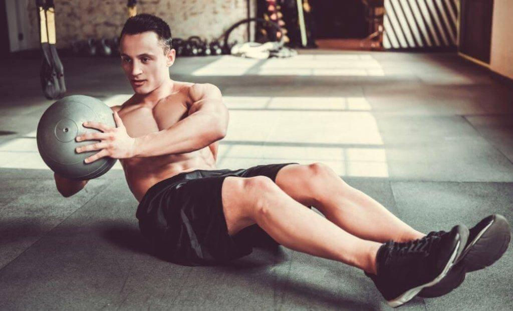 Άνδρας κάνει ασκήσεις με μπάλα γυμναστικής