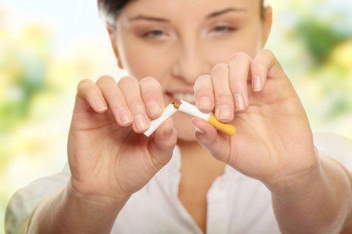 Γυναίκα κόβει τσιγάρο στη μέση