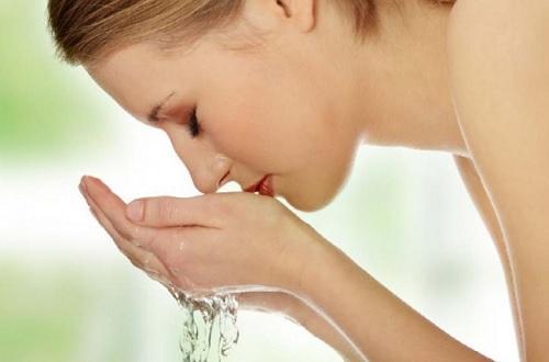 Γυναίκα πλένει με νερό το πρόσωπό της