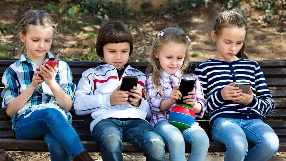 Παιδιά κοιτούν τα κινητά τους τηλέφωνα