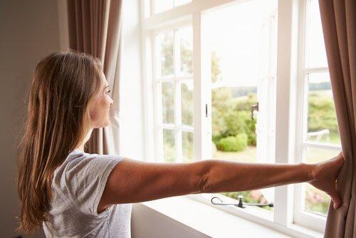 Γυναίκα ανοίγει τις κουρτίνες στο παράθυρο