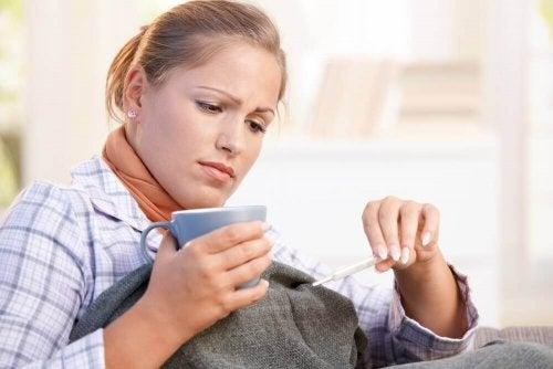 Γυναίκα με πυρετό κοιτά το θερμόμετρο