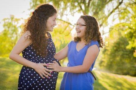Έγκυος μαμά με την κόρη της χαμογελούν