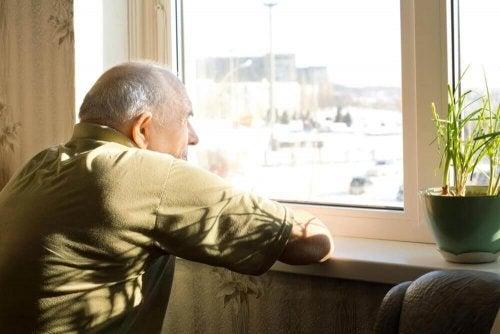 Ηλικιωμένος κοιτά έξω από το παράθυρο