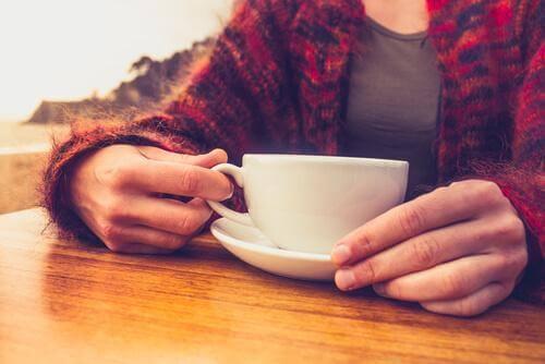 Γυναίκα κρατά κούπα με καφέ