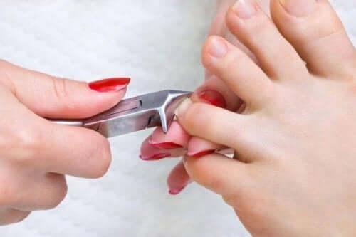 Γυναίκα κόβει τα νύχια του ποδιού της