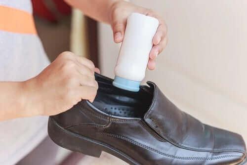 Άτομο βάζει ταλκ στα παπούτσια