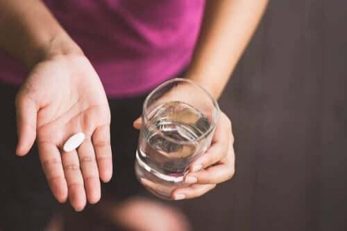 Γυναίκα κρατά χάπι στο χέρι