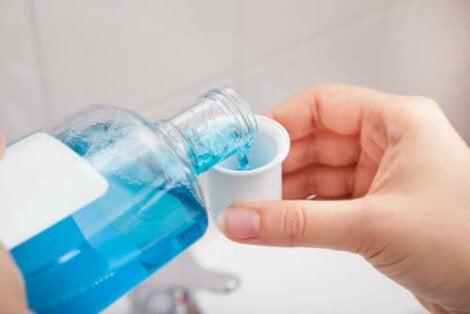 Γυναίκα βάζει στοματικό διάλυμα σε ποτήρι