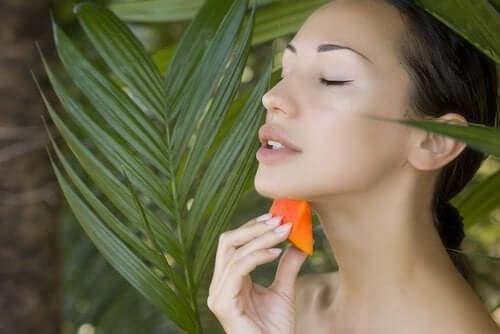 Γυναίκα απλώνει παπάγια στο δέρμα της